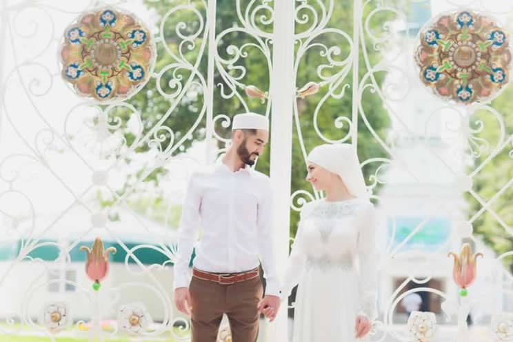 Muslim couple holding hands at wedding