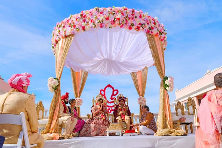 Hindu couple sat outdoors in front of Ganesh being married