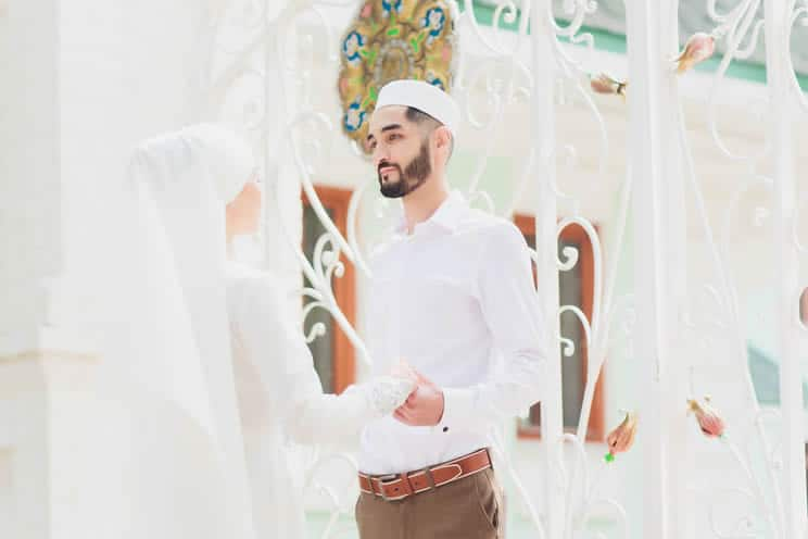 Muslim groom holding hands with bride and staring into each others eyes