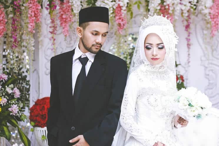 Muslim bride and groom standing back to back
