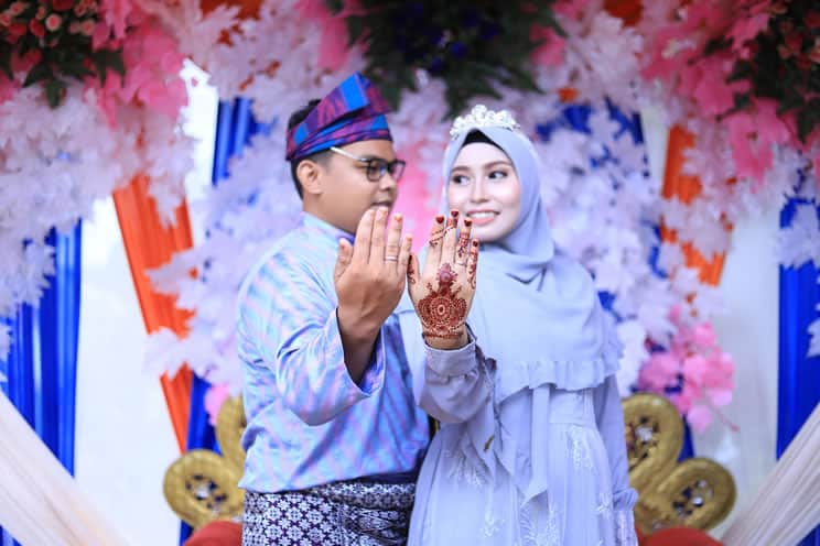 Muslim wedding couple with outstretched arms