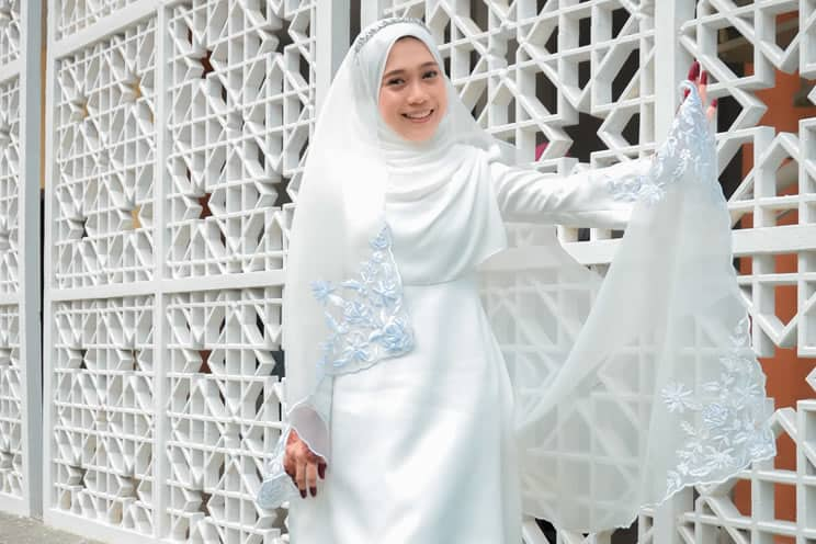 Muslim bride dress in white leaning against a wall