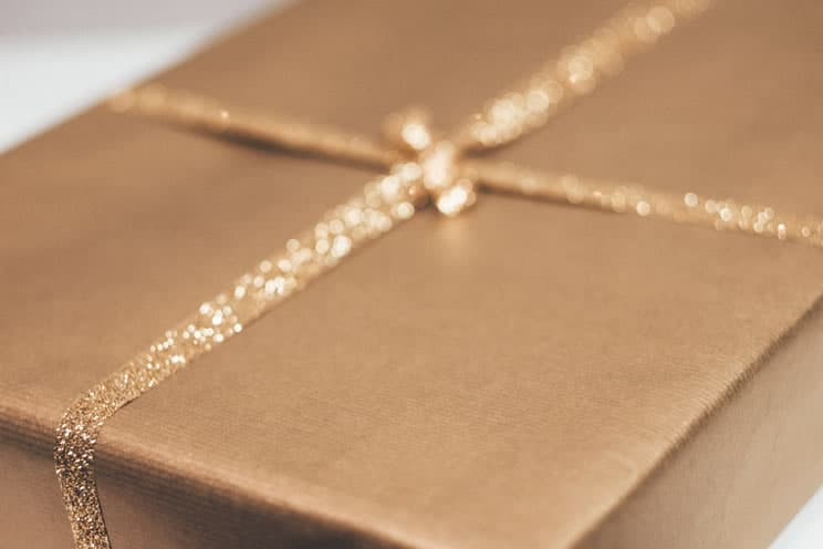 Gold envelope wrapped in a ribbon with a bow